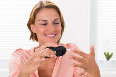 diabetes: Primer De La Mujer Feliz Joven controla el nivel de glucosa con glucómetro