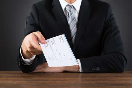 木製のデスクで小切手を与える実業家のクローズ アップ