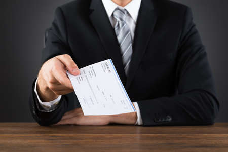 business executive: Close-up Of Businessperson Giving Cheque At Wooden Desk Stock Photo
