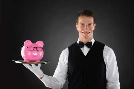 hospitality industry: Portrait Of Happy Butler Holding Tray With Pink Piggybank