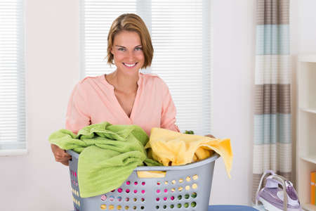 laundry room: Young Happy Woman With Clothes Basket And Electric Iron On Ironing Board