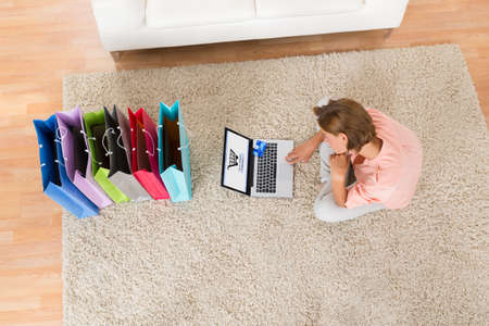 shopping baskets: High Angle View Of Young Woman With Shopping Bags Using Laptop For Online Shopping Stock Photo