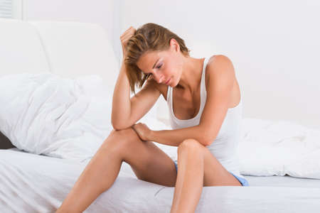tanktop: Depressed Young Woman In Tanktop Sitting On Bed