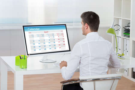 one person: Young Businessman Looking At Calendar On Computer At Desk Stock Photo