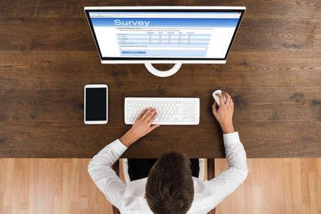 ordinateur bureau: Plongée Of Young Businessman remplissant le formulaire en ligne sur ordinateur Enquête