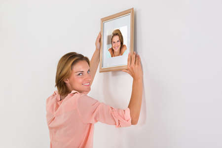 frame wall: Beautiful Happy Woman Putting Picture Frame On Wall Of House