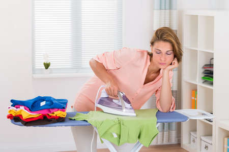 woman ironing: Young Beautiful Woman Ironing Clothes At Home