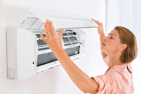 conditions: Young Beautiful Woman Opening Air Conditioner At Home Stock Photo