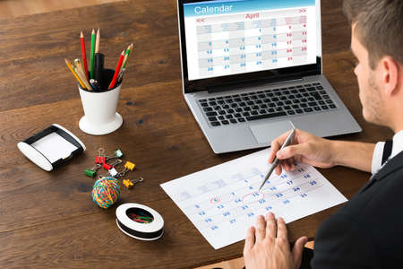 Close-up Of Businessman With Laptop Marking Date On Calendar Stock Photo