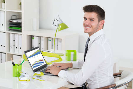 analyzing: Young Businessman Analyzing Graph On Laptop In Office Stock Photo