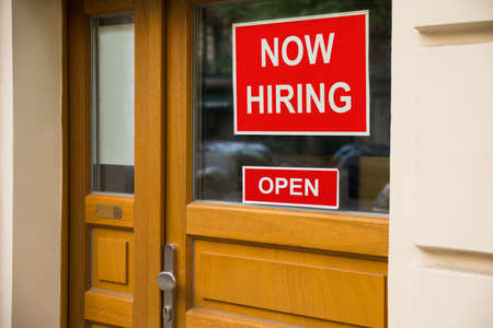 attach: The Text Now Hiring Sticker Attached On Glass Door Of The Office