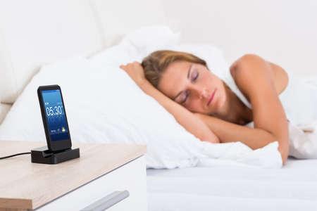 sono: Mulher Jovem dorme na cama com alarme On Mobile Phone Display