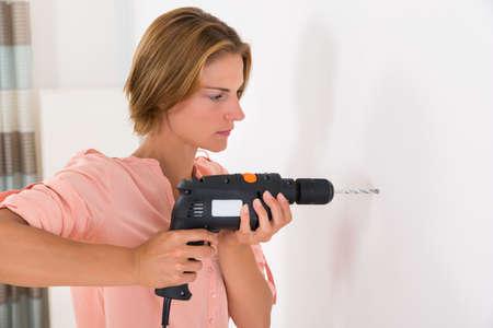 energia electrica: Retrato de la mujer joven que hace agujero en la pared con el taladro de la máquina