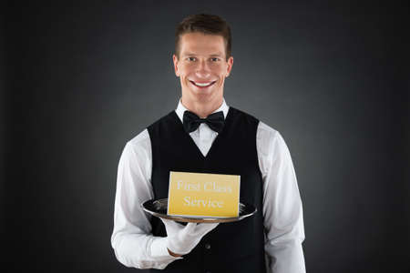 hospitality staff: Young Happy Waiter Holding Plate With The Text First Class Service On Board