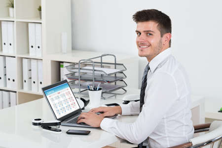 mobile phone screen: Young Happy Businessman Looking At The Calendar On Laptop