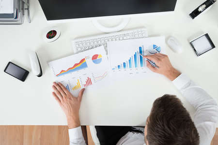analyzing: High Angle View Of Young Businessman Analyzing Financial Graphs Stock Photo