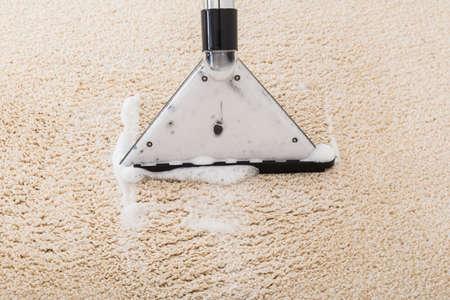 personal de limpieza: Primer plano de la aspiradora con espuma sobre la alfombra mojada