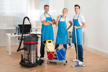 vacuum: Happy Janitors With Vacuum Cleaner And Cleaning Equipments In Office
