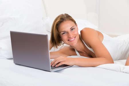 mujer en la cama: Mujer joven feliz con la computadora portátil que miente en cama Foto de archivo