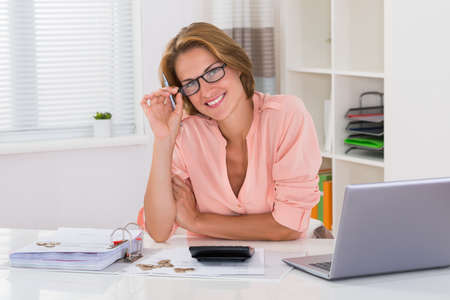 Young Happy Woman With Invoice And Laptop At Desk