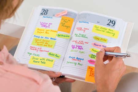 ペンで日記に注意を書く婦人のクローズ アップ