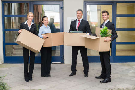 moving office: Happy Group Of Businesspeople With Cardboard Box Moving Into New Office