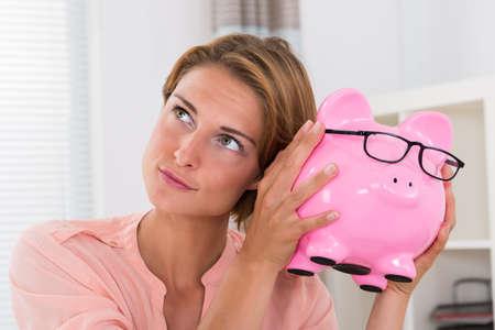 piggybank: Photo Of Young Beautiful Woman Shaking Piggybank Stock Photo