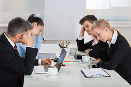 lazy: Team Of Unhappy Businesspeople Sitting In Business Meeting