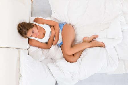 Vista elevada de la mujer joven en la cama que sufren de dolor de estómago