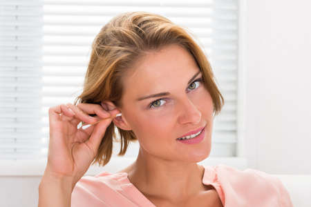 ear buds: Close-up Of Young Woman Cleaning Ear With Cotton Bud