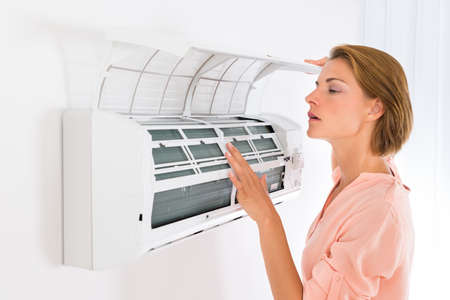 room air: Young Beautiful Woman Opening Air Conditioner At Home Stock Photo