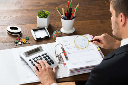 calculadora: El hombre de negocios joven que revisa la factura con la lupa y calculadora en el escritorio Foto de archivo