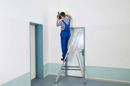 stepladder: Male Electrician Standing On Stepladder Repairing Light Stock Photo
