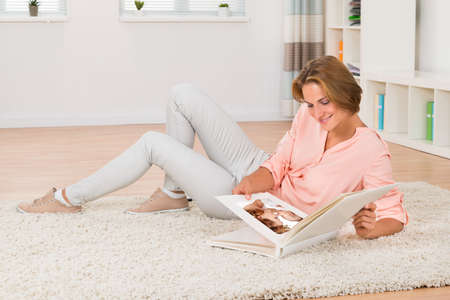 woman laying: Young Woman Sitting On Carpet Looking At Babys Photo At Home