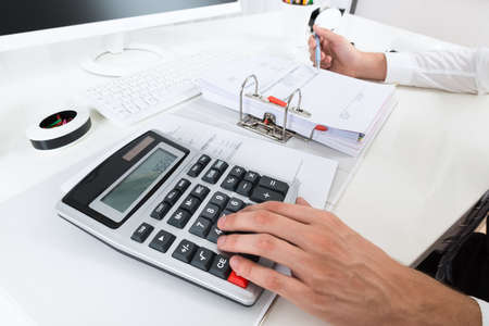 Close-up Of Businessperson Calculating Budget With Calculator At Desk