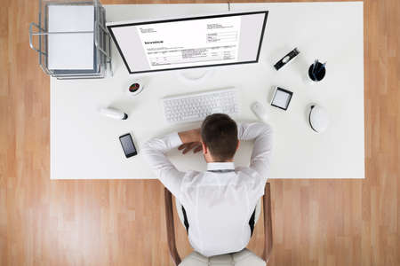 top down: High Angle View Of Young Businessman Sleeping In Front Of Computer At Desk Stock Photo