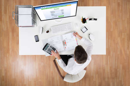 tax returns: High Angle View Of Businessman Calculating Tax In Front Of Computer At Desk Stock Photo