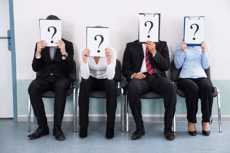 Businesspeople Sitting On Chair Hiding Behind Question Mark Sign Stock Photo