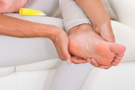 woman foot: Close-up Of Womans Hand Applying Moisturizing Cream On Foot