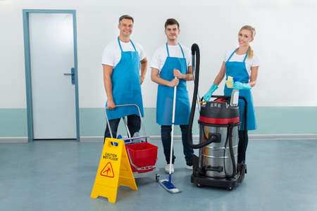 Portrait Of Happy Three Workers With Cleaning Equipments