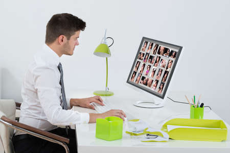 retouch: Young Businessman Editing Images On Computer In Office