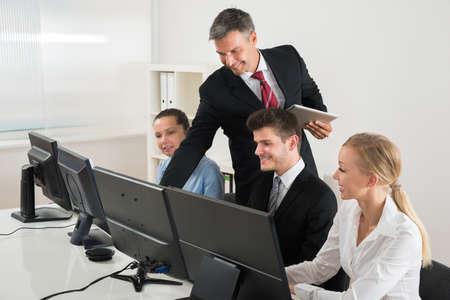 profesor: Profesor Hombre Mostrando Para Empresarios Sobre Computadoras En El Escritorio