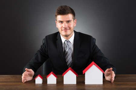 zakelijk: Gelukkige Jonge Zakenman Het beschermen van verschillende grootte van Huis Modellen Bij Bureau Stockfoto