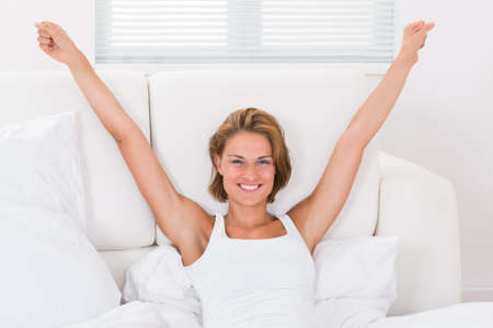 wellness sleepy: Portrait Of Young Happy Woman Stretching Arms In Bed