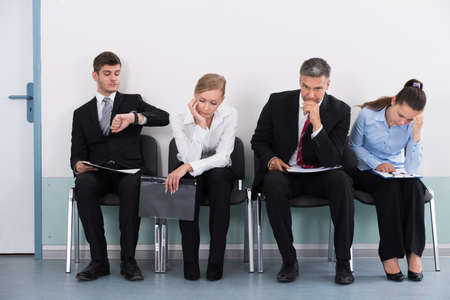 waiting in line: Businesspeople Sitting On Chair Waiting For Job Interview In Office Stock Photo