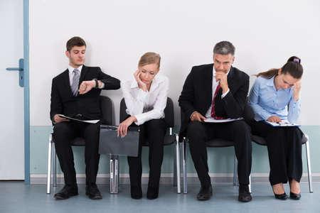 Ondernemers zitten op de stoel wachten op sollicitatiegesprek In Office Stockfoto - 46063098