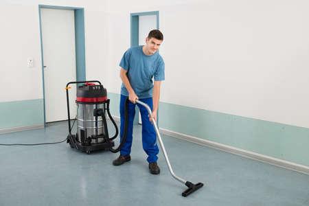personal de limpieza: Joven feliz masculino Trabajador Planta de limpieza con aspiradora Foto de archivo