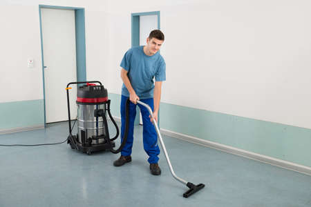 vacuum cleaner: Young Happy Male Worker Cleaning Floor With Vacuum Cleaner