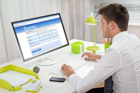Junger Gesch�ftsmann F�llen Online Survey Form auf Computer am Schreibtisch