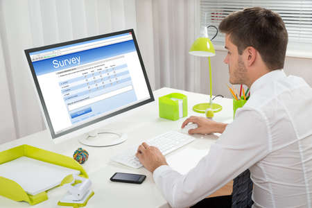 online survey: Young Businessman Filling Online Survey Form On Computer At Desk Stock Photo